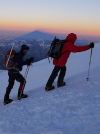 Climbers high on Elbrus with the mountain's shadow.