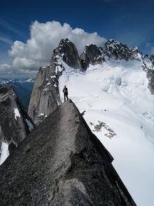 Climber enjoying the view on the W. Ridge of Pigeon Spire in the Bugaboos.