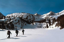 An AAI group skiing into the Rock Creek drainage with Bear Creek Spire behind.