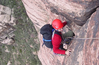 A climber pulls through a roof on Mr. Z (5.7, III). This moderate six-pitch line was established in 2003