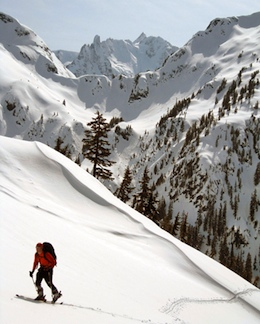 A skier ascends Ruth Mountain with Nooksack Tower and the summit of Mt. Shuksan in the distance.