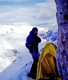A climber settling into a bivy site high on the Cassin Ridge.