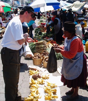 A climber purchasing food in a traditional Ecuadorian market.