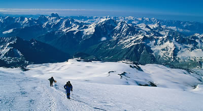 Climbers on Elbrus with the Caucusus behind.