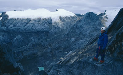 A climbers takes pause to enjoy the view on the ascent of Carstensz Pyramid.