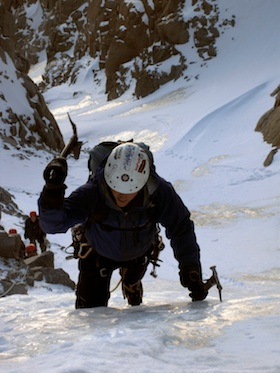 A climber making quality ice axe placements while leading on steep alpine ice