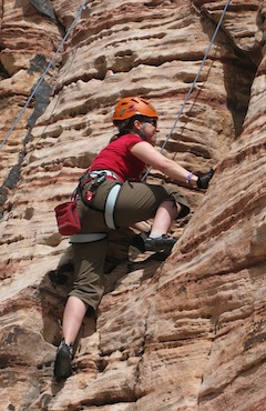 A beginner climber works on movement skills while on top-rope in Red Rock