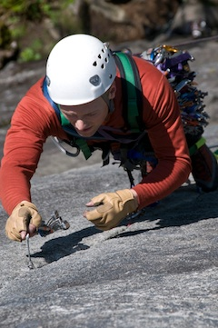 An aid climber carefully places his next piece while climbing at Index.